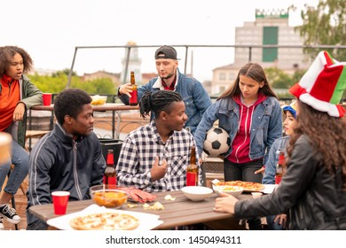 Group of young friendly sports fans gathered together outdoors