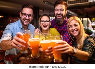 Group of young friends in bar drinking beer toasting