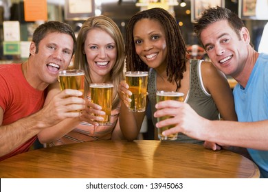 Group of young friends in bar toasting the camera