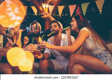 Group of young friends blowing party whistles, drinking beer and having fun at an outdoor New Year's Eve party. Focus on the guy on the right