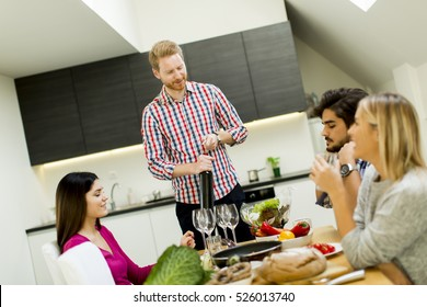 Group of young friends by the dinner table opening bottle of wine