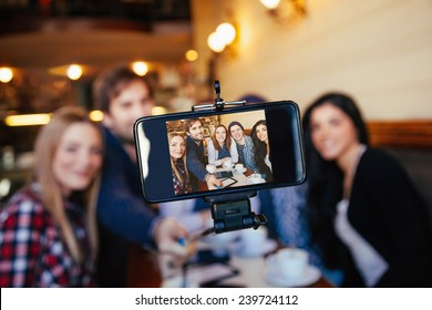 Group Of Young Friends In Cafe Taking Selfie Using Smart Phone And Monopod. Focus Is On Smart Phone