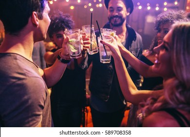 Group of young friends in club toasting with cocktails. Young men and women at nightclub celebrating with drinks.