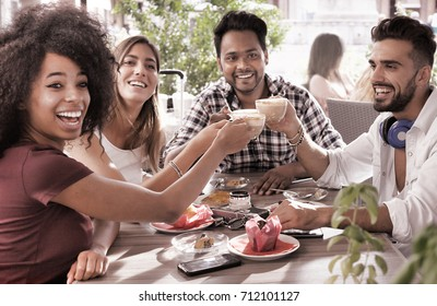 group of young friends at coffee shop drinking cappuccino - concept of diversity and happy friends chilling out in a restaurant. focus on coffee cups