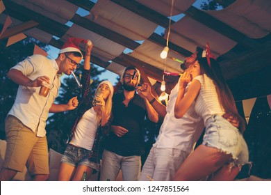 Group of young friends dancing, blowing party whistles, drinking and having fun at an outdoor New Year's Eve party. Focus on the guy in the middle