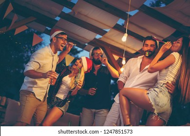 Group of young friends dancing, blowing party whistles, drinking and having fun at an outdoor New Year's Eve party. Focus on the girl on the left