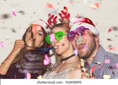 Group of young friends dancing and having fun at New Year's Eve party. Focus on the guy and the girl in the middle