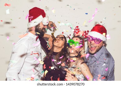 Group of young friends dancing, making funny faces, blowing party whistles and having fun at New Year's Eve party