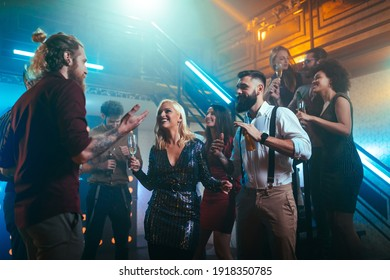 Group of young friends drinking alcohol and having fun at the nightclub