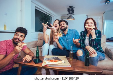 Group of young friends eating pizza and watching tv.Home party.Fast food concept.