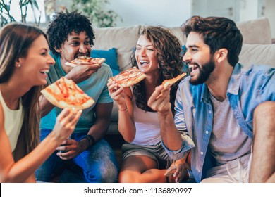 Group of young friends eating pizza, selective focus.Home party.
