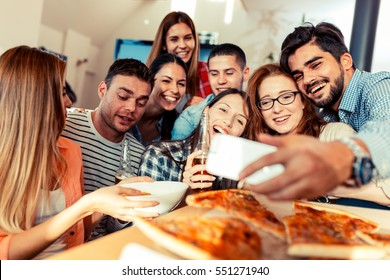 Group of young friends eating pizza and making selfie with smart phone.Party.
