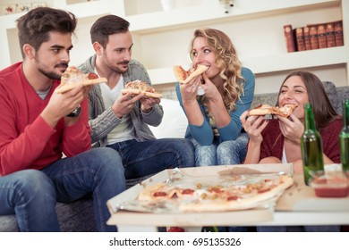 Group of young friends eating pizza in home interior.