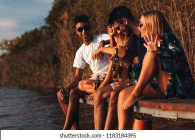 Group of young friends enjoying a day at the lake. They sitting on pier talking and drinking beers.