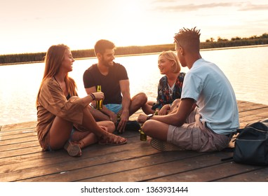Group of young friends enjoying a day at the lake. They sitting on pier talking, laughing and drinking beers.