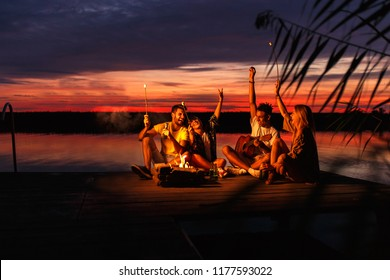 Group of young friends enjoying at the lake at night. They sitting around the fire singing and having fun.