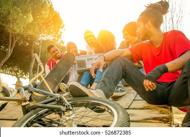 group of young friends gathering outside for fun chilling sitting on ground listening to music.  happy youngsters meeting in the park. concept of togetherness and diversity.with sunburst effects.