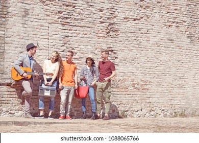 group of young friends hanging out in town having fun standing against a brick wall chilling out playing guitar. concept of youth culture, street fashion and cozy lifestyle