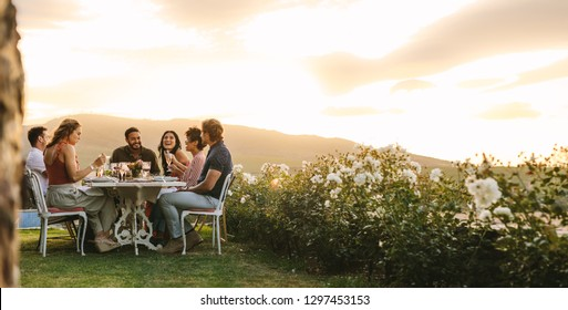Group of young friends hanging out with drinks at outdoors dinner party. Young men and women sitting around a table having food and drinks.