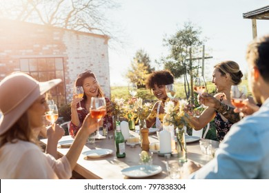 Group of young friends hanging out with drinks at outdoors party. Young men and women sitting around a table toasting wine.