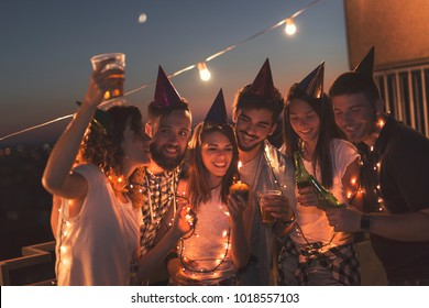 Group of young friends having a birthday party at a building rooftop, singing a song and blowing a candle. Focus on the birthday girl