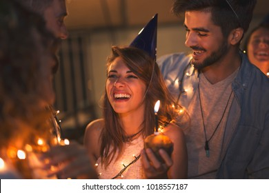 Group of young friends having a birthday party at a building rooftop, singing a song and blowing a candle