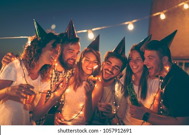 Group of young friends having a birthday party at a building rooftop, singing a song and blowing a candle. Focus on the candle and people on sides