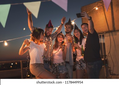 Group of young friends having a birthday party at a building rooftop, singing a song, blowing a candle and taking a selfie