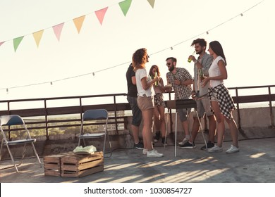 Group of young friends having fun at rooftop party, making barbecue and enjoying hot summer days. Focus on the guy in the middle