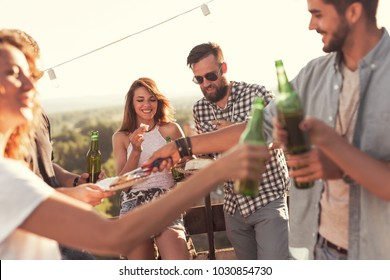 Group of young friends having fun at rooftop party, drinking beer, eating barbecue and enjoying hot summer days
