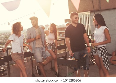 Group of young friends having fun at rooftop party, making barbecue, drinking beer and enjoying hot summer days. Focus on the man next to a barbecue