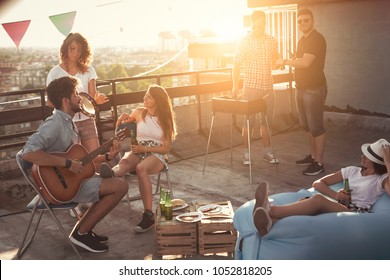 Group of young friends having fun at rooftop party, making barbecue, drinking beer and enjoying hot summer days. Focus on the girl sitting on the chair