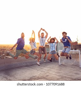 Group of young friends having fun on a building rooftop after a football match; jumping, all caught in the air with the cityscape and sunset in the background