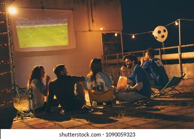 Group of young friends having fun while watching a football match on a building rooftop. Focus on the guy eating popcorn