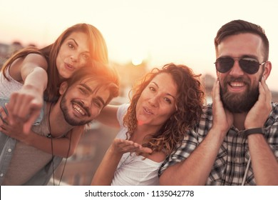 Group of young friends having fun on a summertime rooftop party. Focus on the girl sending kisses