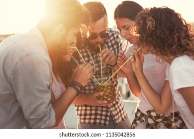 Group of young friends having fun at rooftop party, enjoying beautiful sunset over the city and drinking a pineapple cocktail. Focus on the couple in the middle