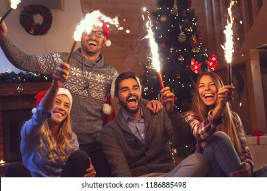Group of young friends having fun at a New Year's celebration, holding sparklers at a midnight countdown. Focus on the guy sitting in the middle