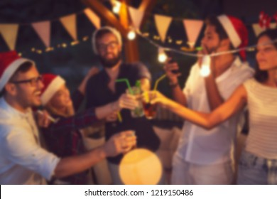 Group of young friends having fun at an outoodr poolside New Year's Eve party, making a midnight countdown toast. Blurred people background