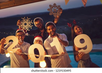Group of young friends having fun at a New Year's Eve outdoor pool party, dancing and holding cardboard snowflakes and numbers 2019