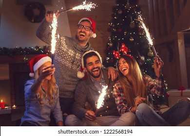 Group of young friends having fun at a New Year's celebration, holding sparklers at a midnight countdown
