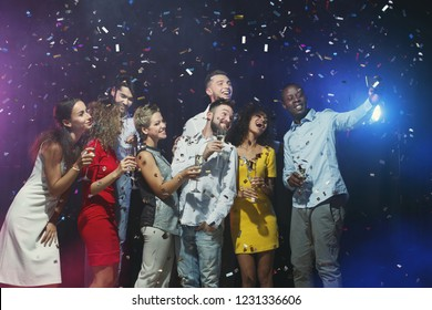 Group of young friends having fun and taking selfies at birthday party