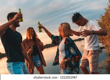 Group of young friends having fun drinking beer and dancing on pier by the lake at sunset.
