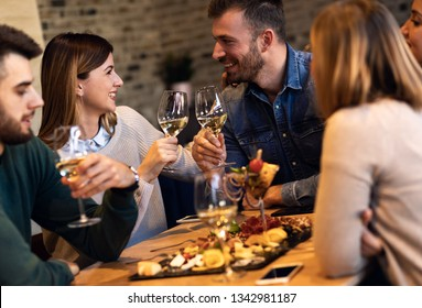 Group of young friends having fun in restaurant, talking and laughing while toasting with glass of wine.
