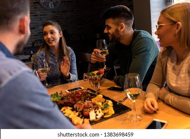 Group of young friends having fun in restaurant, talking and laughing while dining at table.