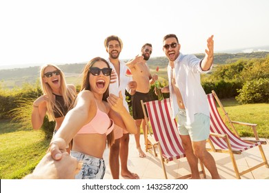 Group of young friends having fun at a poolside summertime party, drinking beer and inviting more friends to join them