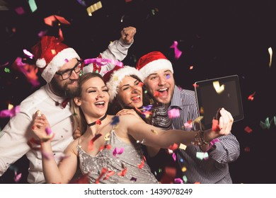 Group of young friends having fun at New Year's Eve party and making crazy faces and taking selfies