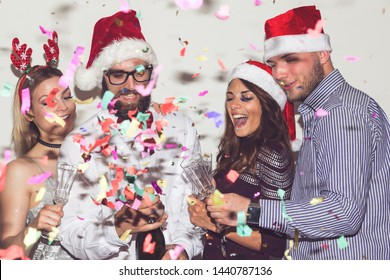 Group of young friends having fun at New Year's Eve party, opening a bottle of champagne and making a midnight toast. Man with the bottle in focus