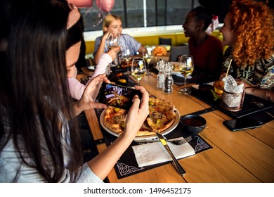 Group of young friends having fun in restaurant, talking and laughing while dining at table. Girl taking picture of food.