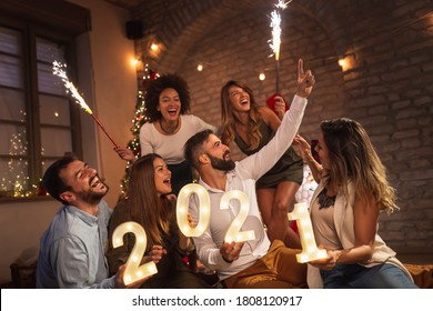 Group of young friends having fun at New Years party, holding illuminative numbers 2021 representing the upcoming New Year and waving with sparklers at midnight countdown