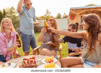 Group of young friends having fun at backyard barbecue party, drinking beer and enjoying sunny summer days outdoor